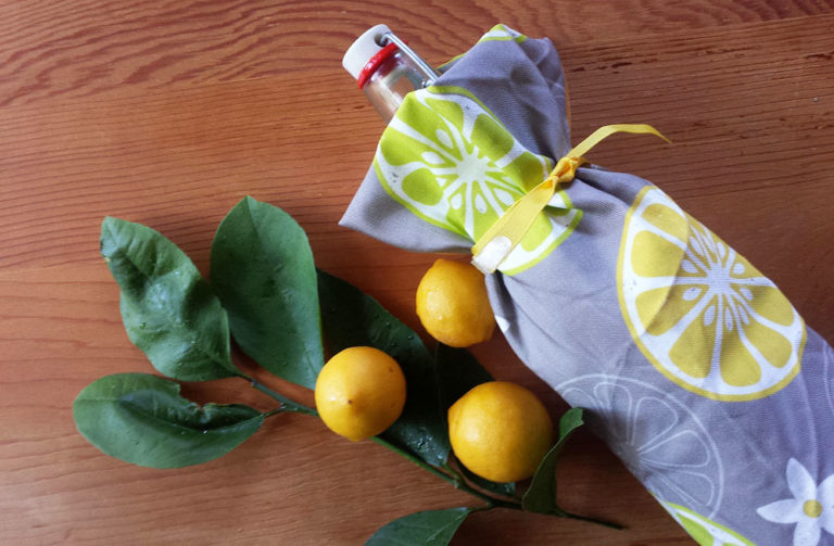 Bottle gift wrapped with Orange, Orange, Lemon, Lime tea towel by Lellobird