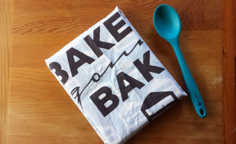 Cookbook gift wrapped with Bakers Gonna Bake tea towel by Lellobird